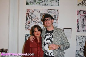 Annie Preece and Johnny Otto pose in front of one of Otto's paintings at the Ashley Paige Bikini Factory. Photo courtesy of SunofHollywood.com